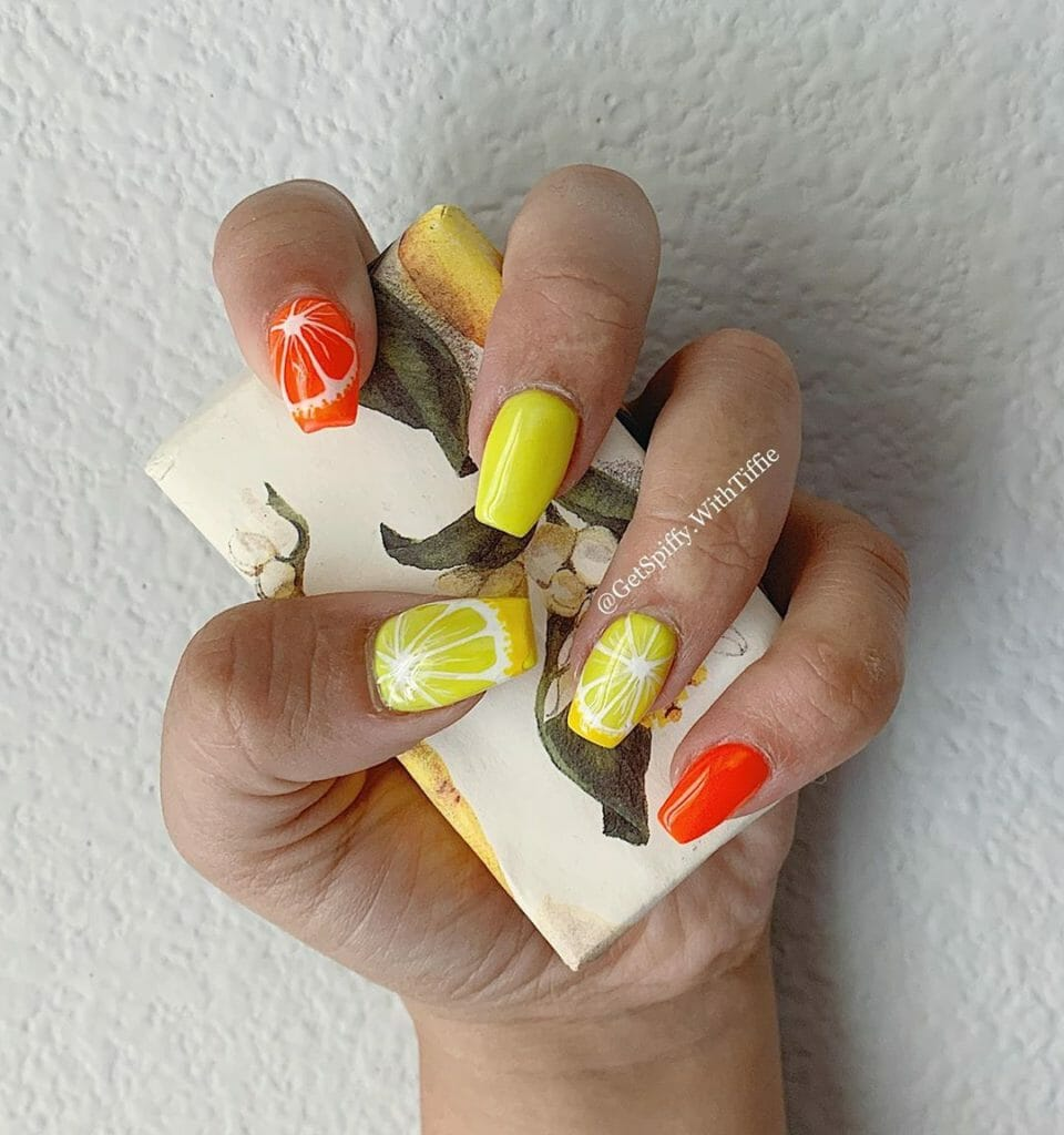 yellow and orange nails with an orange or lemon slice